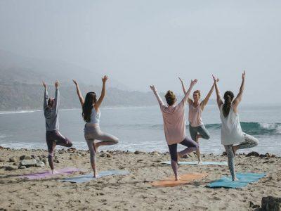 cours de yoga sur la plage posture de l'arbre vrkshasana